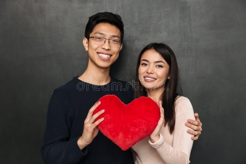 Gelukkig Aziatisch paar die samen terwijl het houden van hartstuk speelgoed stellen royalty-vrije stock fotografie