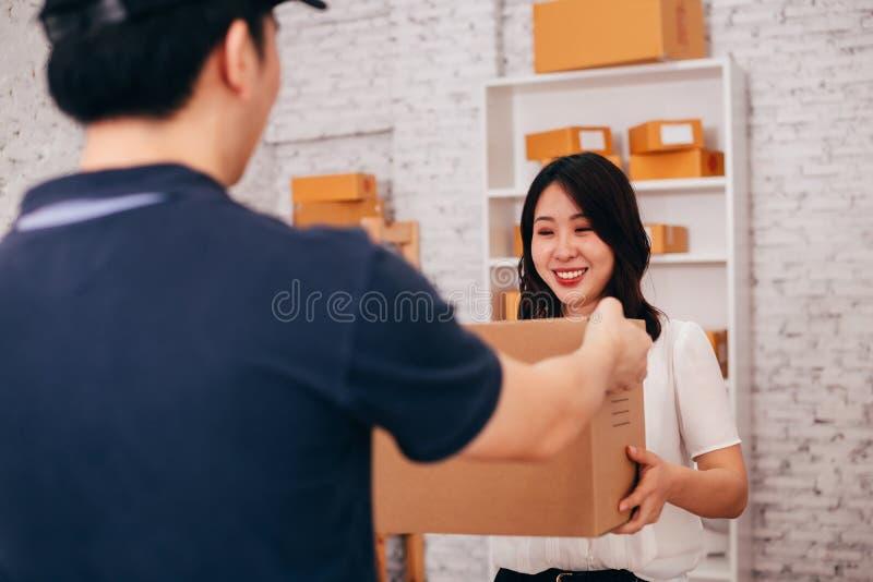 Gelukkig Aziatisch volwassen bedrijfswijfje in het bureau die een pakket van mannelijke deliverman ontvangen stock fotografie