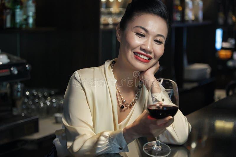 Gelukkig Aziatisch wijfje die wijnglas bekijken stock afbeeldingen