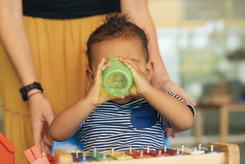 Gelukkig baby drinkwater en het spelen stock fotografie