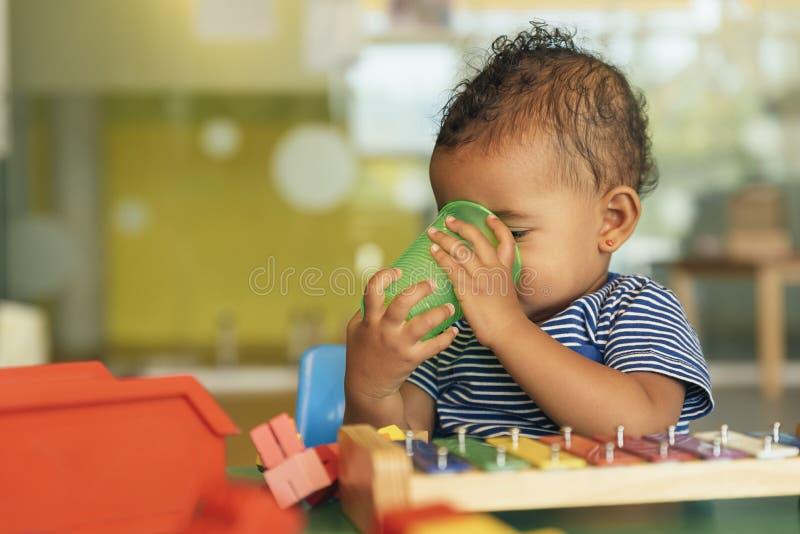 Gelukkig baby drinkwater en het spelen stock foto's