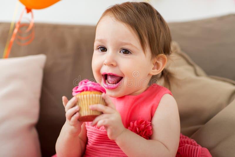 Gelukkig babymeisje die cupcake op verjaardagspartij eten stock afbeeldingen