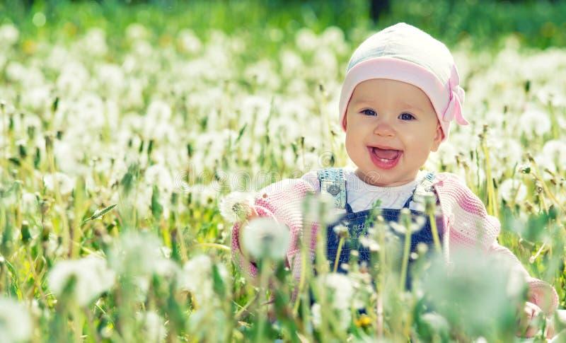 Gelukkig babymeisje op weide met witte bloemen op de aard stock afbeelding