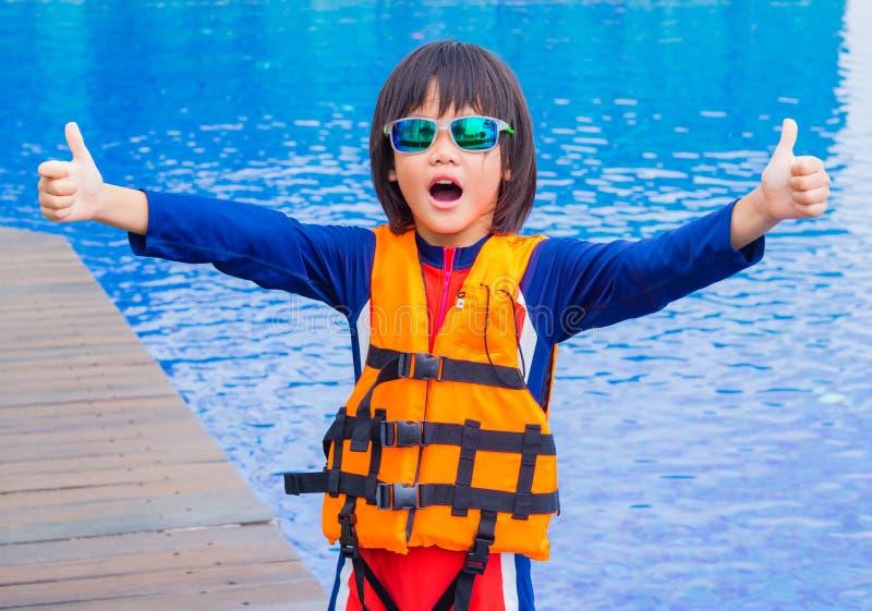 Gelukkig beduimelt weinig jongen met oranje reddingsvest heeft omhoog pret en geniet van in het zwembad stock foto