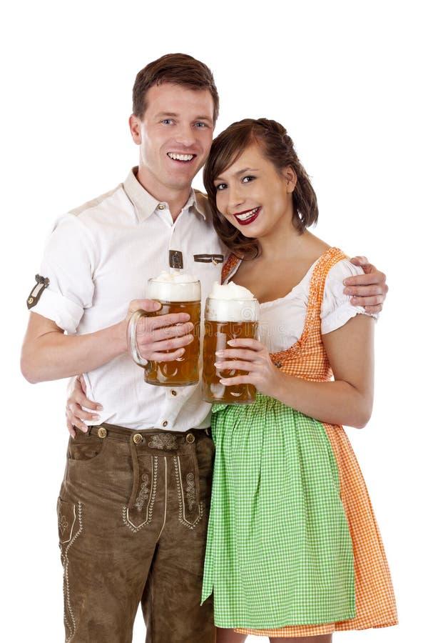 Gelukkig Beiers paar met Oktoberfest bierstenen bierkroes stock foto's
