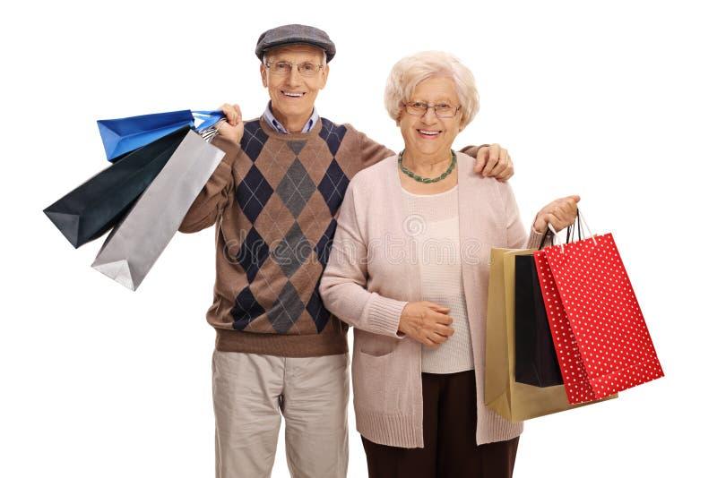 Gelukkig bejaard paar met het winkelen zakken stock foto's