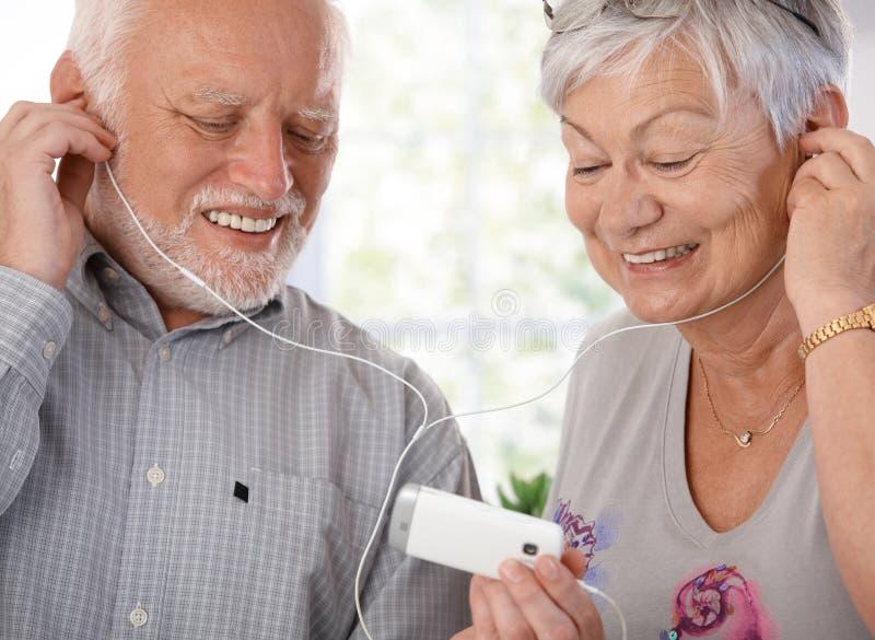Gelukkig bejaard paar met mp3 speler stock afbeelding