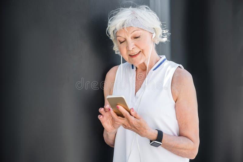 Gelukkig bejaarde die mobiele telefoon voor mededeling met behulp van openlucht royalty-vrije stock afbeeldingen