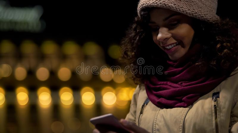 Gelukkig biracial meisje die in goede stemming in boodschapper met vriend, het lachen babbelen stock foto's