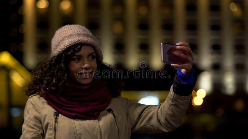 Gelukkig biracial meisje die selfie tegen de achtergrond van de nachtstad nemen om geheugen te bewaren royalty-vrije stock foto