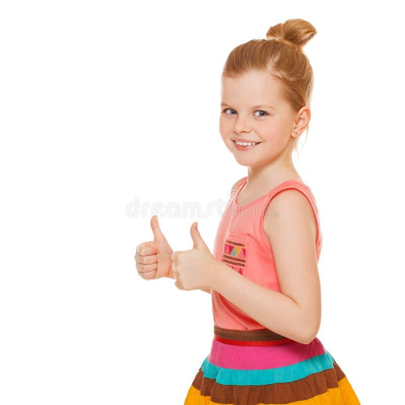Gelukkig blij meisje die tonend duimen glimlachen die, op witte achtergrond worden geïsoleerd stock afbeeldingen