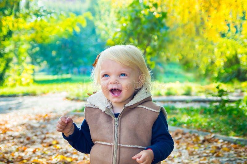 Gelukkig blond babymeisje op natuurlijke achtergrond van autum stock foto's
