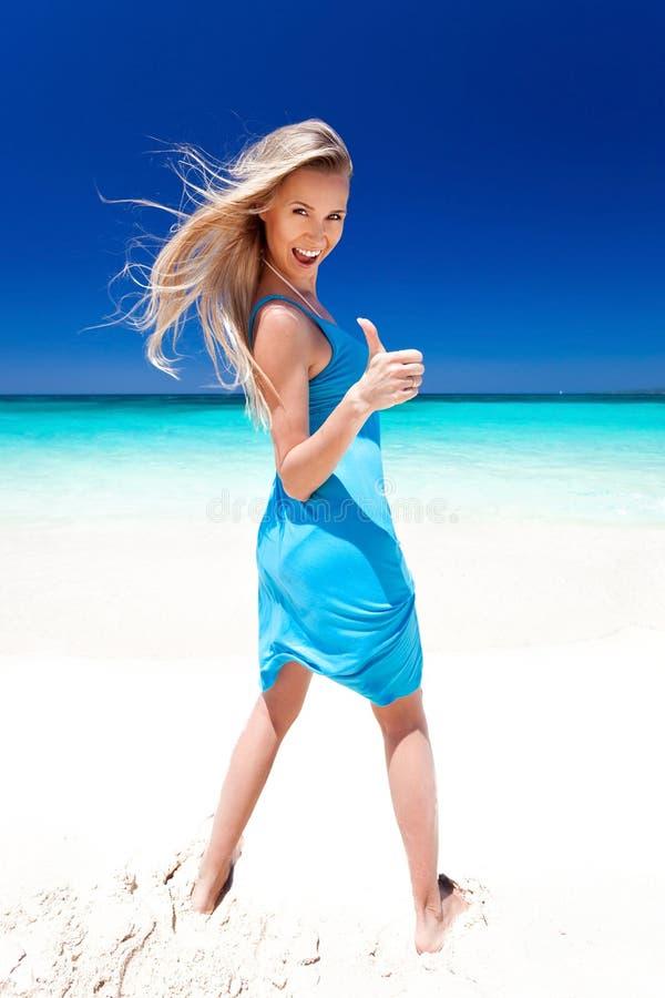 Gelukkig blond meisje op strand, die okeyteken tonen. royalty-vrije stock afbeeldingen