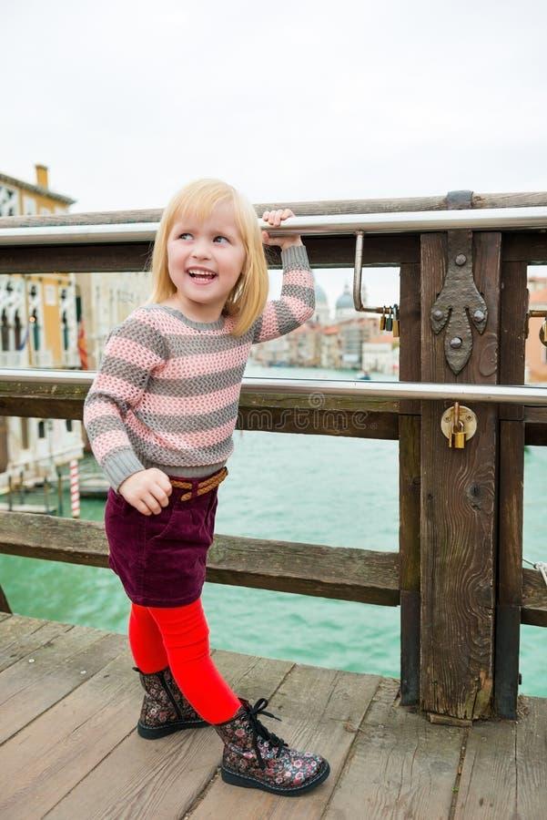 Gelukkig blondemeisje die over schouder op brug in Venetië kijken stock foto