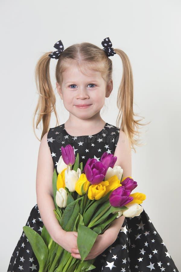 Gelukkig blondemeisje met tulpen stock afbeelding