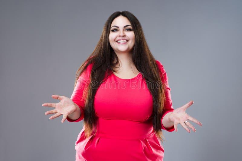 Gelukkig brunette plus groottemodel in rode kleding, vette vrouw met lang haar op grijze achtergrond, lichaams positief concept stock afbeeldingen