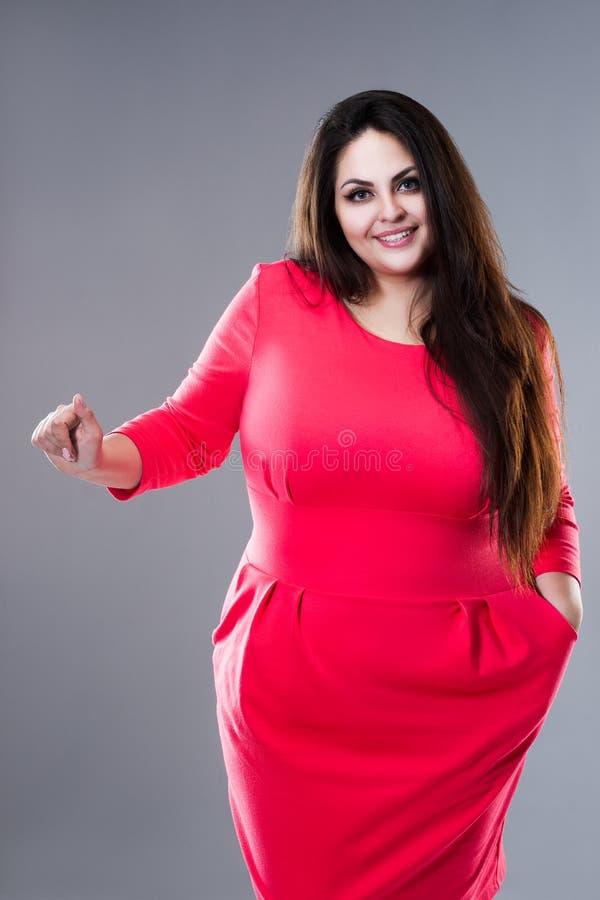 Gelukkig brunette plus groottemodel in rode kleding, vette vrouw met lang haar op grijze achtergrond, lichaams positief concept royalty-vrije stock foto's