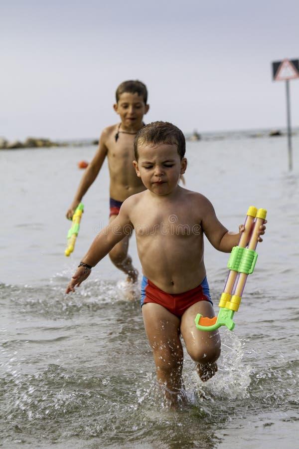 Gelukkig childsspel in overzees met watergun, vakantie in Italië royalty-vrije stock foto