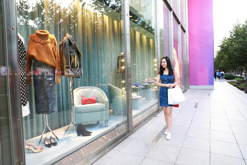 Gelukkig Chinees Oostelijk oosters jong in de vrouwenmeisje die van Azië in wandelgalerij met zakken het winkelen vensterachtergr stock foto