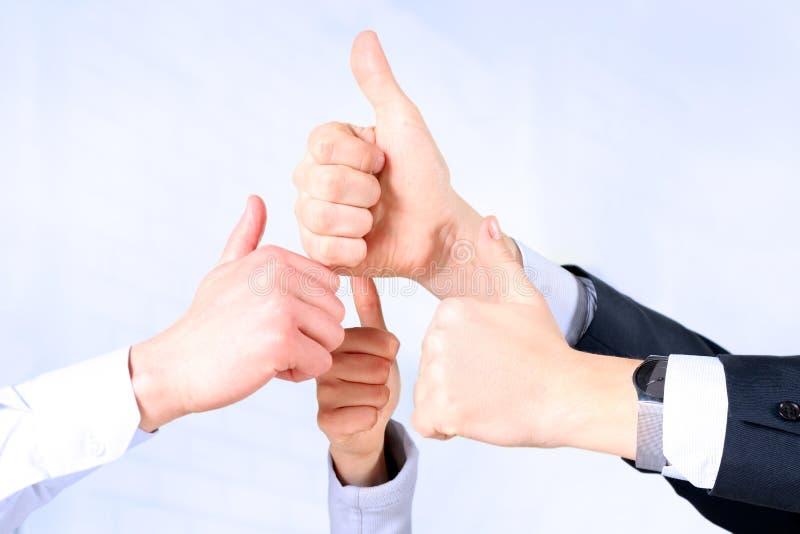 Gelukkig commercieel team die duimen in bureau tonen stock afbeeldingen