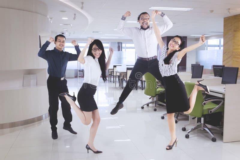 Gelukkig commercieel team die in het bureau springen stock foto's