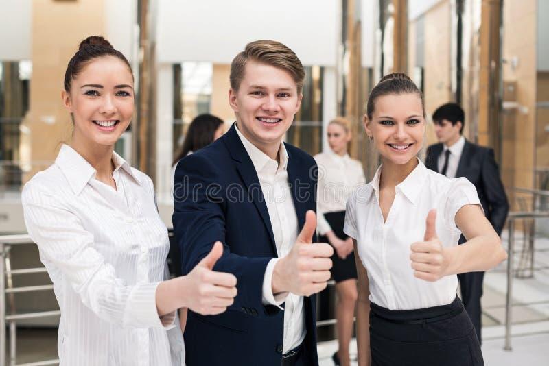 Gelukkig commercieel team met omhoog duimen stock afbeeldingen