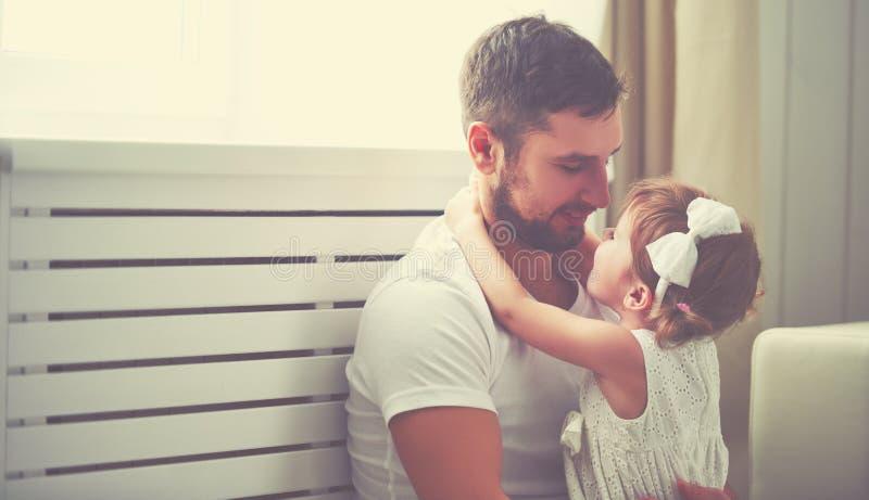 Gelukkig de babymeisje van het familiekind in wapens van zijn vader thuis stock foto
