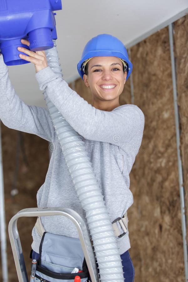 Gelukkig de ventilatiesysteem van de vrouwelijke werknemermontage in gebouwenplafond royalty-vrije stock afbeelding