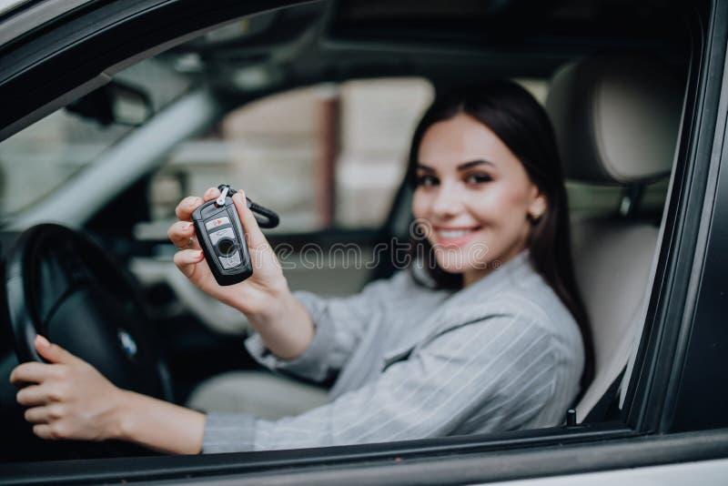 Gelukkig de vrouw van de leerlingsbestuurder jong het glimlachen portret met autosleutels stock fotografie