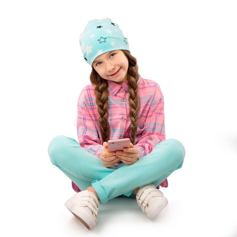Gelukkig die meisje met smartphonezitting op vloer op witte achtergrond wordt geïsoleerd Mensen, kinderen, technologieconcept royalty-vrije stock foto's