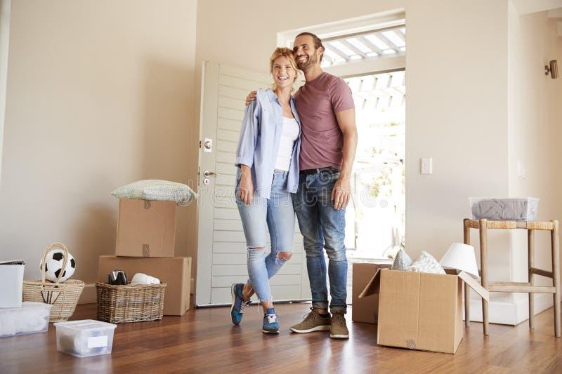 Gelukkig die Paar door Dozen in Nieuw Huis bij het Bewegen van Dag wordt omringd stock foto's