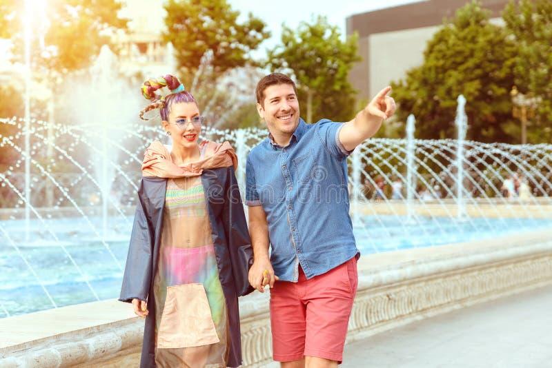 Gelukkig divers paar die in de handen van de liefdeholding avond van gang op stadsstraat genieten stock foto's