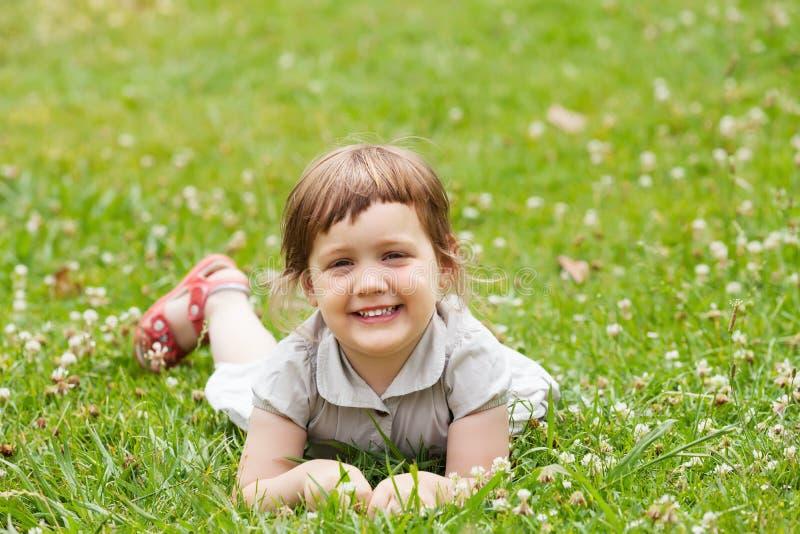 Gelukkig driejarig meisje binnen   grasweide royalty-vrije stock afbeelding