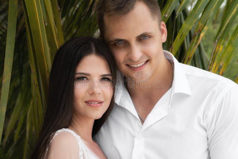 Gelukkig echtpaar De jonggehuwden bevinden zich onder de bladeren van palmen stock afbeelding