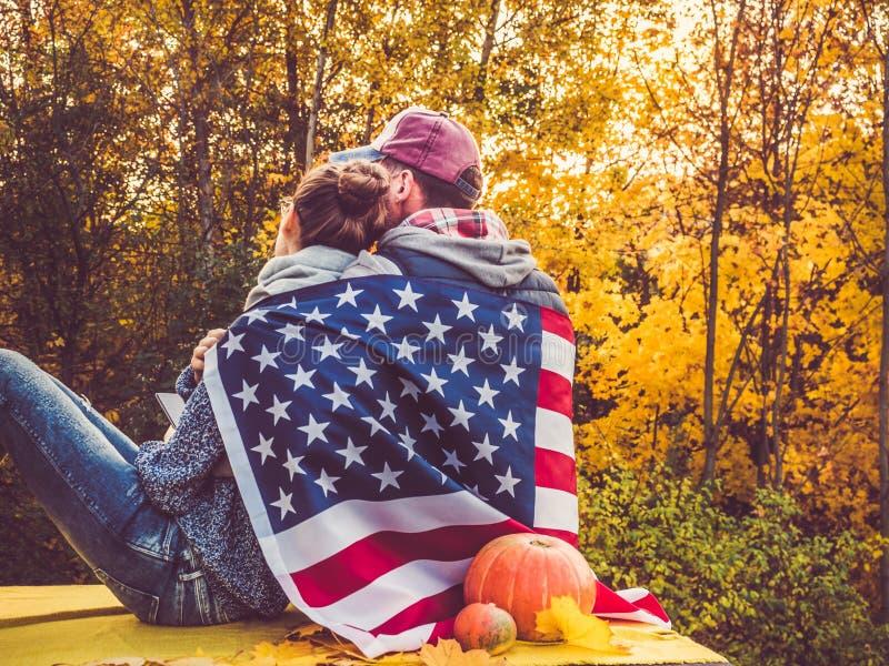 Gelukkig echtpaar die de vlag van de V.S. houden stock fotografie