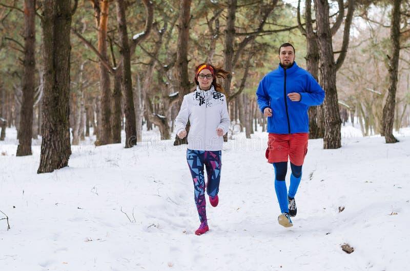 Gelukkig echtpaar die rond in de winterbos lopen royalty-vrije stock fotografie