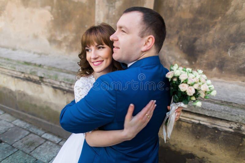 Gelukkig echtpaar die samen naar de toekomst dichtbij bruine muur van oude kerk kijken, close-up royalty-vrije stock foto