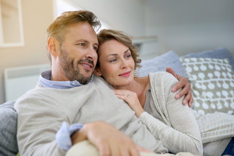 Gelukkig echtpaar die thuis ontspannen stock foto