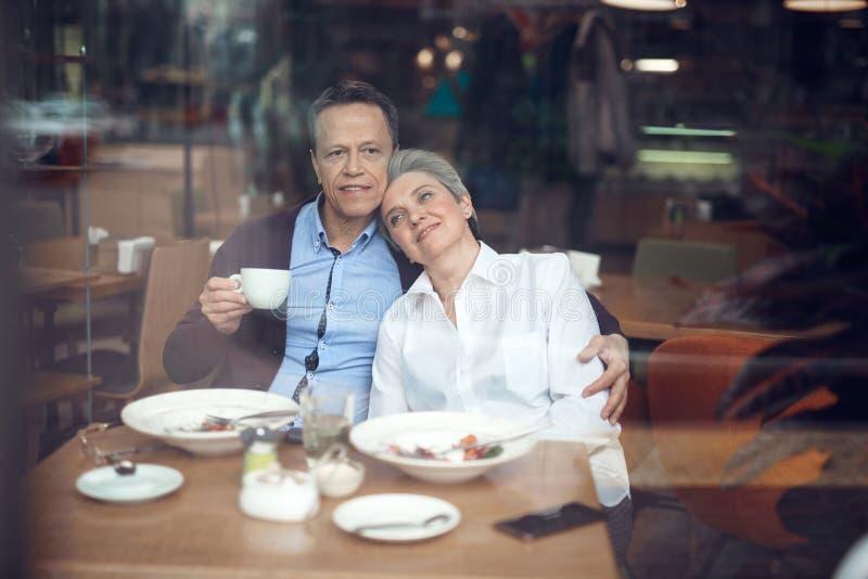 Gelukkig elegant oud paar dat van diner in koffie geniet stock fotografie