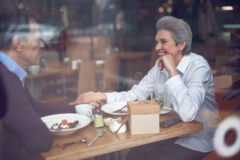 Gelukkig elegant oud paar dat van vergadering in koffie geniet royalty-vrije stock afbeelding