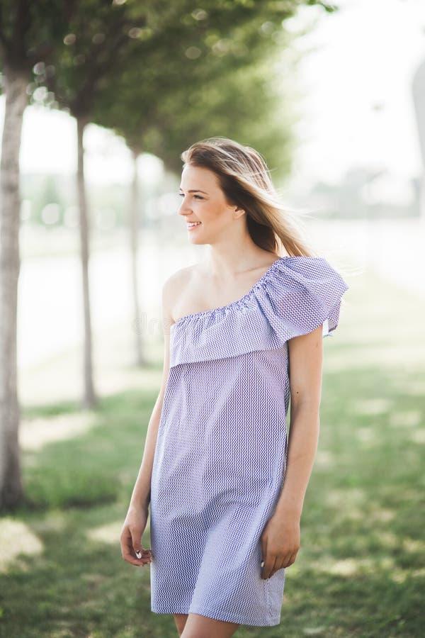 Gelukkig en aantrekkelijk mooi artistiek jong meisje in kleding in de zomertuin het stellen voor camera stock fotografie