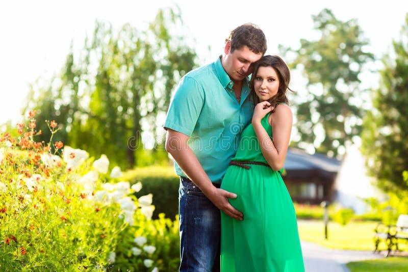 Gelukkig en jong zwanger paar die in aard koesteren royalty-vrije stock fotografie