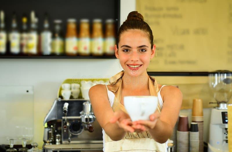 Gelukkig en Leuk Barista dient kop van hete koffiedrank Vrouwenbarista in koffiewinkel Mooie vrouwentribune achter koffie stock foto