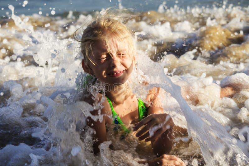 Gelukkig en mooi blond meisje in een groen zwempak die op het strand onder de golven liggen royalty-vrije stock afbeeldingen