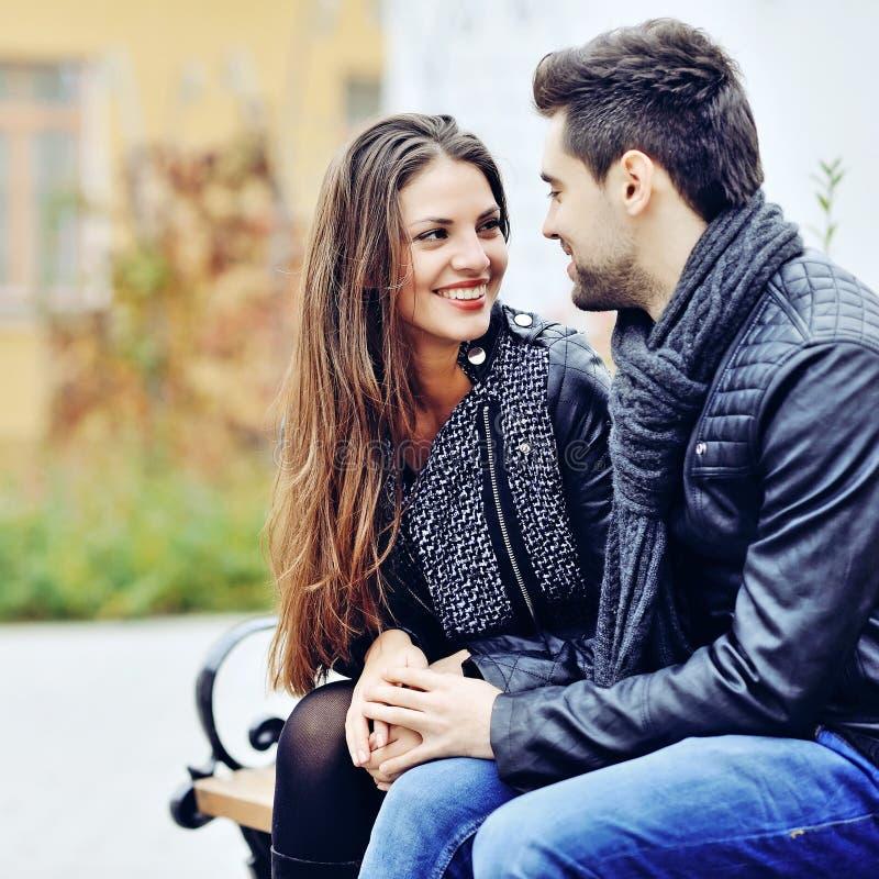 Gelukkig en paar die elkaar in openlucht glimlachen kijken royalty-vrije stock fotografie