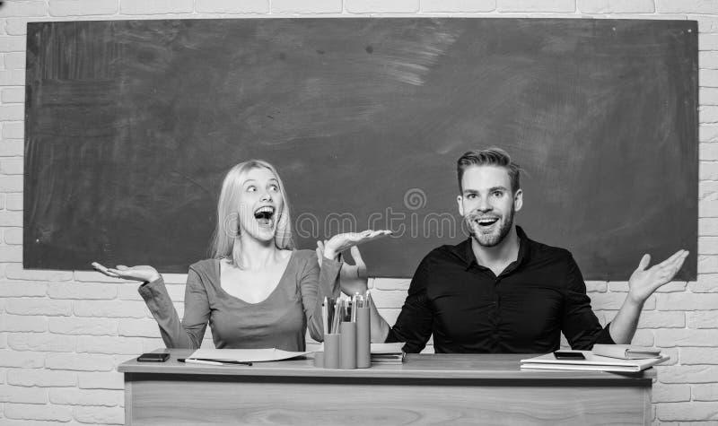 Gelukkig en vrolijk Mooie leraar en knappe schoolmeester die bij bureau glimlachen Universiteit of studenten hoog stock afbeeldingen