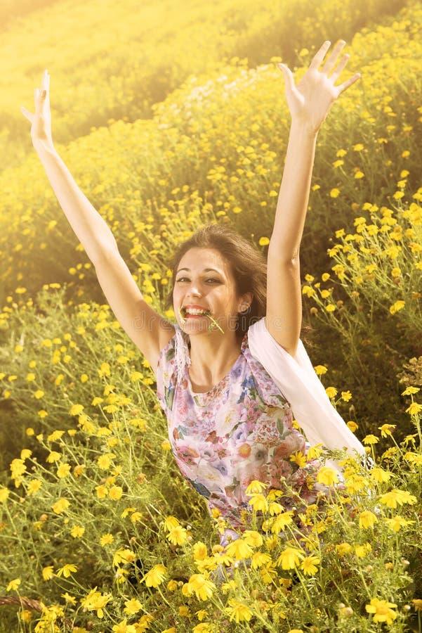 Gelukkig exultant meisje op een bloemgebied stock fotografie