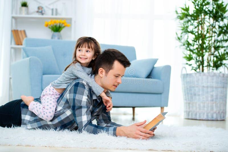 Gelukkig familie en van de vader dagconcept Papa met dochter het besteden tijdsamenhorigheid thuis Leuk meisje op de rug van de p stock foto's