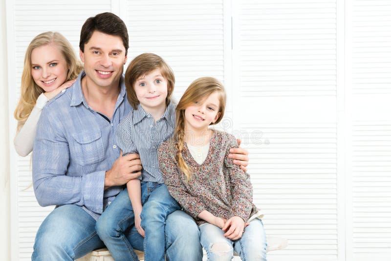 _gelukkig familie van vier plakken aan elkaar en glimlachen stock foto's
