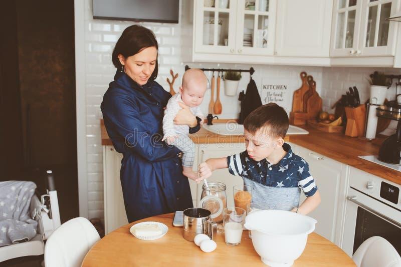 Gelukkig familiebaksel samen in moderne witte keuken Moeder, zoons en babydochter het koken in comfortabele weekendochtend royalty-vrije stock afbeelding